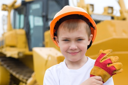Boy in helmet is against the background of a large excavator. photo