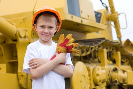 Boy in a helmet is against the background of a large excavator. photo