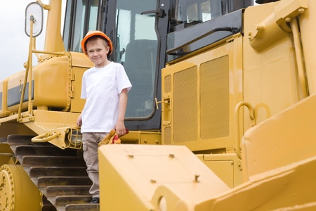 Smiling boy in a helmet is a large excavator. photo