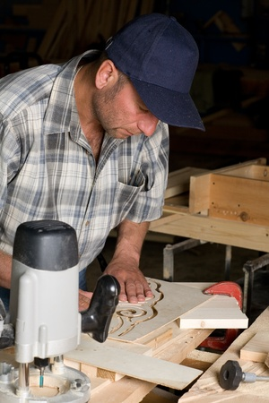 Carpenter working on the production of decorative detail. photo