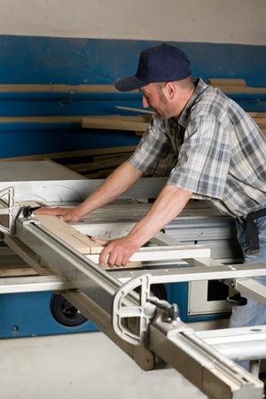 carpenter's sawdust: Carpenter working on woodworking machines in carpentry shop.