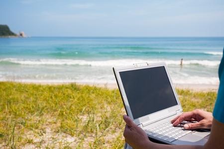 Frau, die Hände auf dem Laptop gegen das Meer.