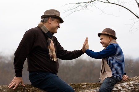 Grandfather and grandson playing outdoors. Autumn. Stock Photo