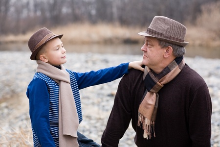 Grandfather and grandson looking at each other. Autumn. At the river. photo