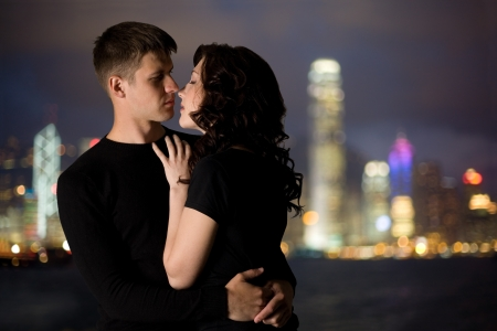 Loving young couple in the background lights of the night city. photo
