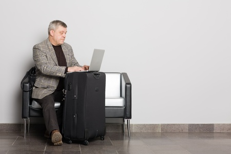 Pending a middle aged man using a laptop. Stock Photo - 11720615