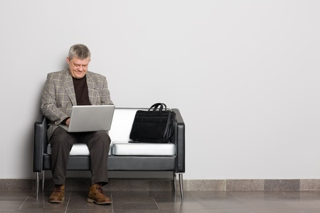 Smiling middle aged man using a laptop in the waiting room. photo