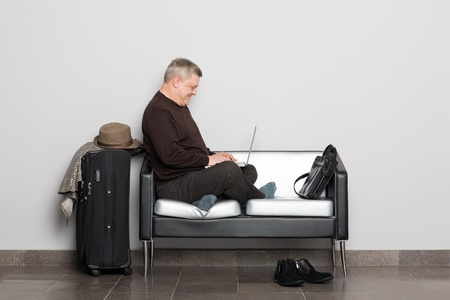 Elegant middle aged man uses a laptop. Waiting hall. photo