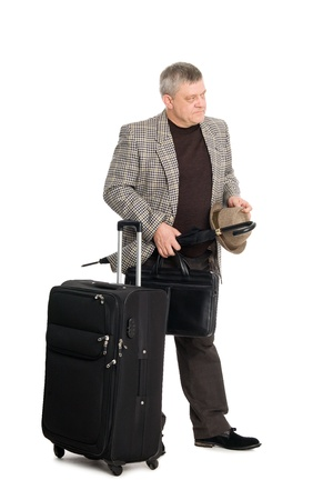 Man in a checkered suit and luggage looks away. photo