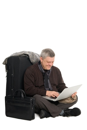 Mature man in anticipation of landing on aircraft operating the laptop. photo