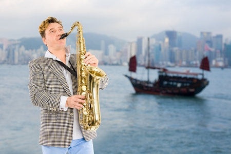 Young musician with saxophone in the background of Hong Kong. photo