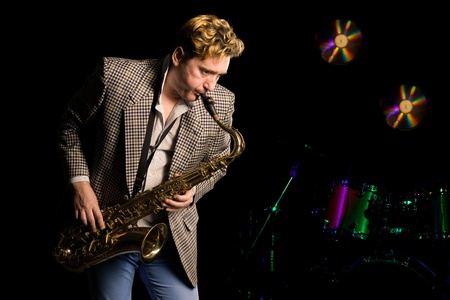 Young jazz musician with saxophone. In the background, music drums kit. photo
