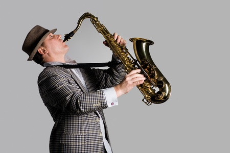 Young man playing the saxophone on a gray background. photo