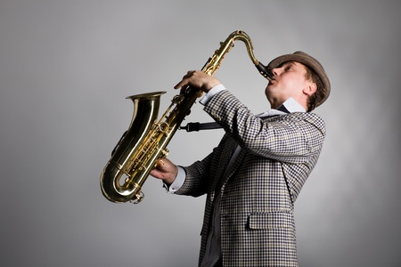 Saxophonist playing on the background of gray wall. photo