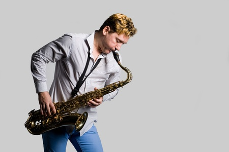 Saxophonist playing on the background of gray. Stock Photo