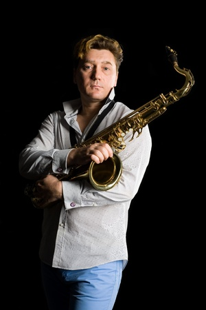 Portrait of a young saxophonist on a black background. photo