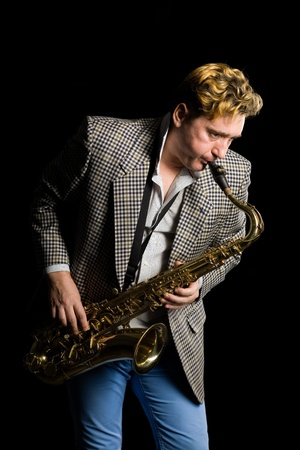 Young musician plays the saxophone. photo