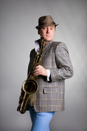 Young musician with saxophone in the background of gray wall. photo
