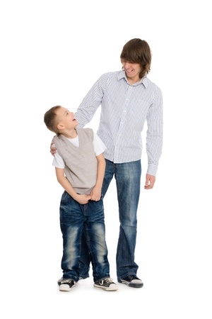 younger: Elder and younger brothers, happily smiling. Isolated on white.