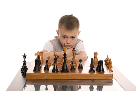 Little boy plays chess. Isolated on white. photo