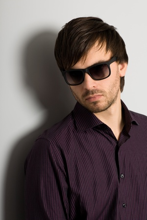 Portrait of stylish young man wearing sunglasses photo