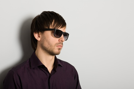Stylish young man wearing sunglasses photo