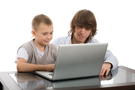 Elder brother teaches his younger brother working on the laptop. Stock Photo - 12020416