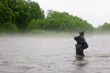 Fisherman caught a salmon. Rain. Fog. Morning.