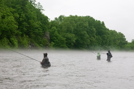Fishermen catch salmon in a mountain river. Is rain. Fog. Stock Photo - 12064937