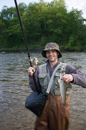 Happy fisherman holds salmon(char). Morning. Stock Photo - 12064940