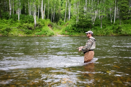 rivers mountains: Fisherman catches of salmon and trout in the river.