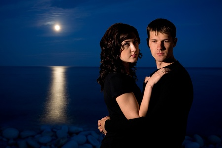 Young couple in love in the moonlight by the sea photo
