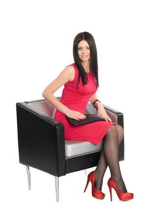 Smiling young brunette sitting on a chair Stock Photo - 12331868