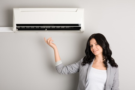 Beautiful brunette shows up on a new air conditioner Stock Photo - 12331902