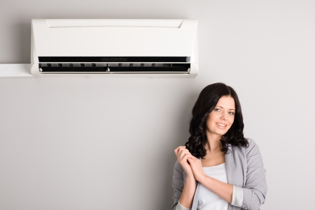 cold air: Beautiful girl standing next to the air conditioner