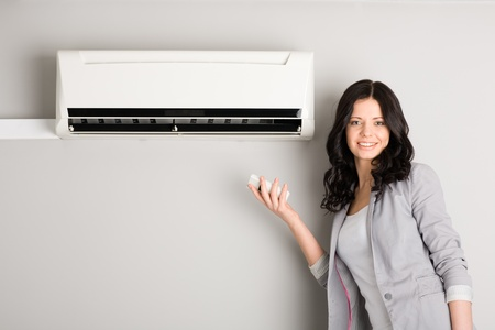 cold air: Beautiful girl holding a remote control near the air conditioner