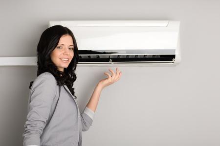 fresh air: Hermosa muchacha sonriente que muestra el aparato de aire acondicionado