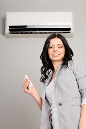 Beautiful girl with a remote control air conditioning is
