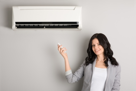 condicionador: Beautiful girl holding a remote control air conditioner