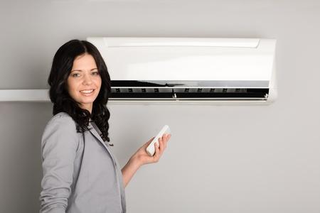 aire acondicionado: Hermosa chica con un aire acondicionado con control remoto