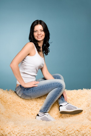 Smiling girl in jeans sitting on the couch photo