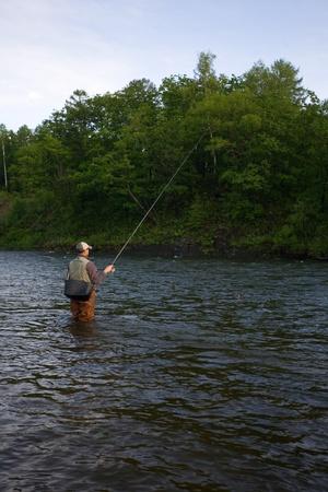 Fisherman catches of salmon on a mountain river. Stock Photo - 12600221