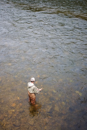 Fisherman catches of salmon on a mountain river photo