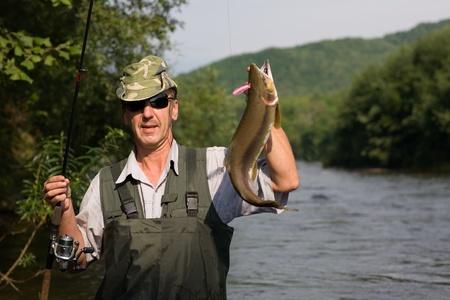 coger: Feliz pescador atrap� un salm�n (salm�n rosado) en el r�o