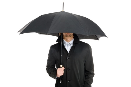 elegant business man in a raincoat standing under an umbrella  photo