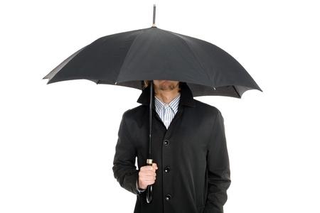 elegant business man: uomo d'affari elegante in un impermeabile in piedi sotto un ombrello Archivio Fotografico