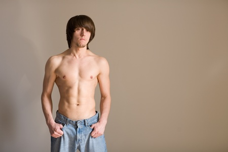 Semi-naked  young man against the wall. photo