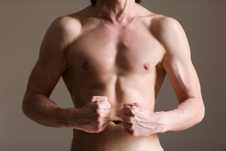 beefcake: Healthy muscular young man against a wall Stock Photo