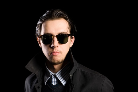 Stylish young man wearing sunglasses on a black background. photo