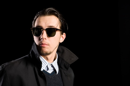 stylish young man wearing sunglasses looking away. photo